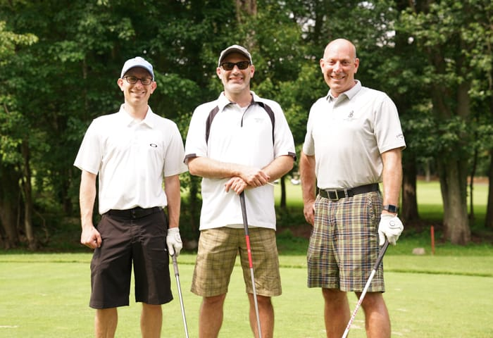 Three alumni men golfing